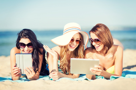 internet  concept: summer holidays, technology and internet concept - girls in bikinis with tablet pc sunbathing on the beach