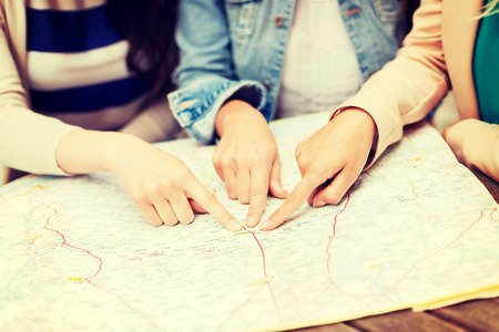 tourism: holidays and tourism concept - women with tourist map in the city