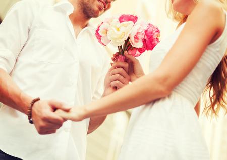 romance: wakacje, miłość, relacje i randki koncepcja - para z bukietem kwiatów w mieście