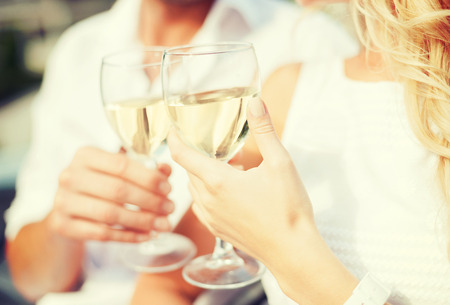 toasting: summer holidays and dating concept - couple drinking wine in cafe in the city