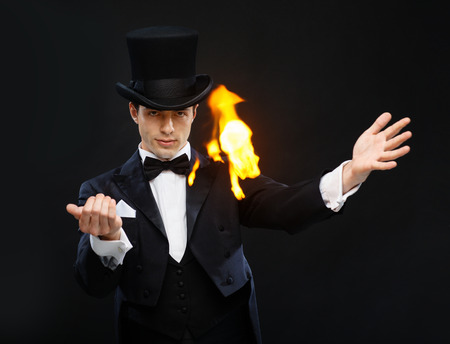 conjuring: magic, performance, circus, show concept - magician in top hat showing trick with fire