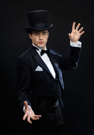 black tie: magic, performance, circus, show concept - magician in top hat showing trick
