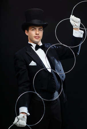 illusionist: magic, performance, circus, show concept - magician in top hat showing trick with linking rings