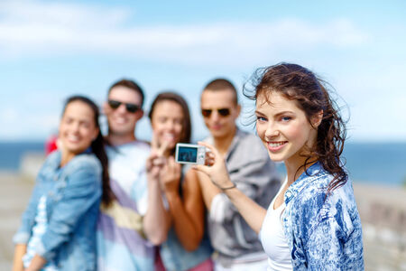 summer holidays and teenage concept - group of happy teenagers taking photo outside photo