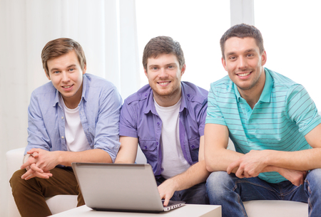 friendship, technology and home concept - smiling male friends with laptop computer at home Фото со стока