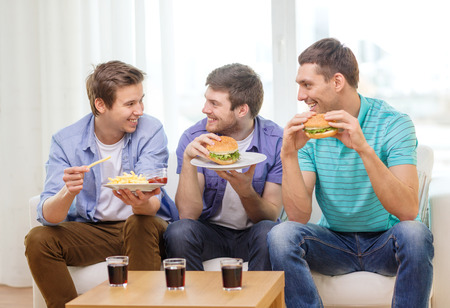 friendship, food and leisure concept - smiling friends with soda and hamburgers at home photo
