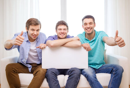 friendship and advertising concept - smiling male friends holding white blank board and showing thumbs up photo
