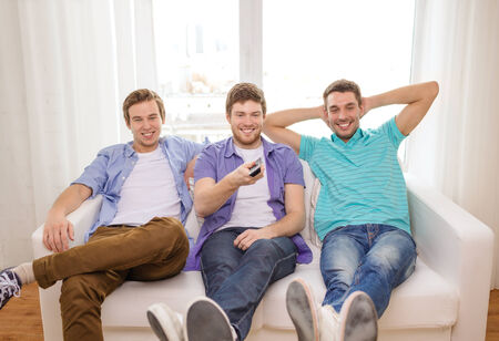 room mate: friendship, technology and home concept - smiling male friends with remote control at home Stock Photo