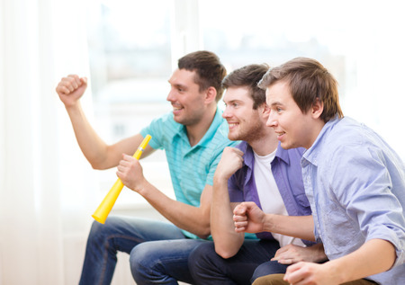 cheering fans: friendship, sports and entertainment - happy male friends with vuvuzela watching sports at home Stock Photo