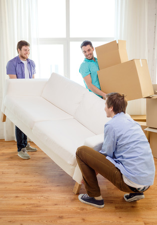 moving home: moving, real estate and friendship concept - smiling male friends with sofa and boxes at new home
