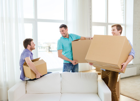 moving box: moving, real estate and friendship concept - smiling male friends carrying boxes at new place