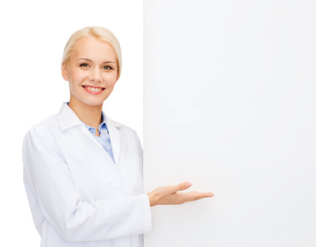 healthcare, advertisement and medicine concept - smiling female doctor with white blank board photo