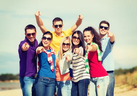 invitando: verano, vacaciones, vacaciones, feliz a la gente concepto - grupo de amigos que se divierten en la playa y apuntando a usted