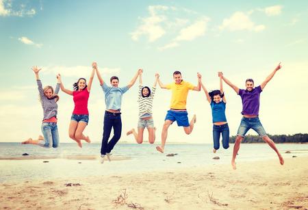 de zomer, vakantie, gelukkige mensen concept - groep vrienden springen op het strand