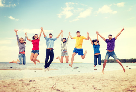 boy friend: summer, holidays, vacation, happy people concept - group of friends jumping on the beach Stock Photo