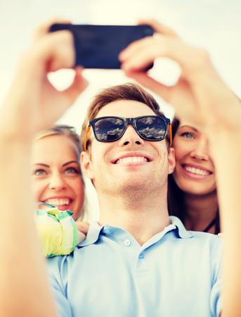 group picture: summer, holidays, vacation and happiness concept - group of friends taking picture with smartphone