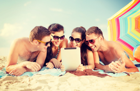 summer, holidays, vacation, technology and happy people concept - group of smiling people in sunglasses with tablet pc on the beach