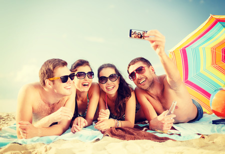 women having fun: summer, holidays, vacation, technology and happiness concept - group of smiling people in sunglasses taking picture with smartphone on beach