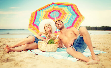 summer, holidays, vacation and happy people concept - smiling couple lying on the beach under colorful umbrella and sunbathing photo
