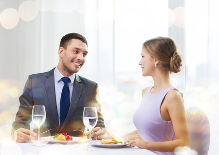 up to date: restaurant, couple and holiday concept - smiling couple eating main course at restaurant Stock Photo