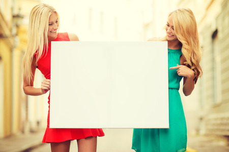 summer holidays, , travel, tourism and advertisement concept - two happy blonde women with blank white board in the city photo