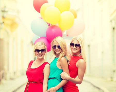 street party: holidays and tourism, friends, hen party, blonde girls concept - three beautiful women with colorful balloons in the city