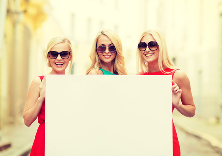 summer holidays, , travel, tourism and advertisement concept - three happy blonde women with blank white board in the city photo