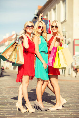 sale and tourism, happy people concept - beautiful blonde women with shopping bags in the ctiy photo