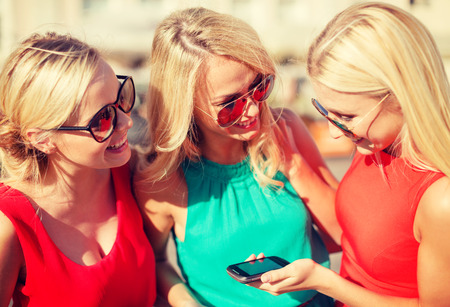 bachelorette party: holidays and tourism, modern technology concept - beautiful blonde girls with smartphone in the city