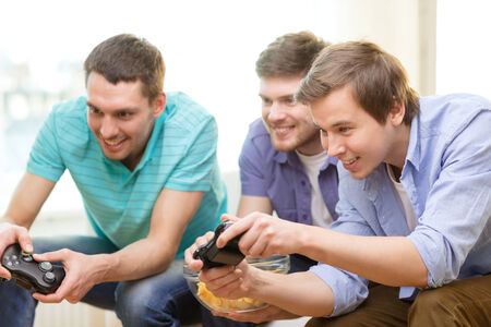 game control: friendship, technology, games and home concept - smiling male friends playing video games at home