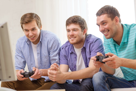 video games: friendship, technology, games and home concept - smiling male friends playing video games at home