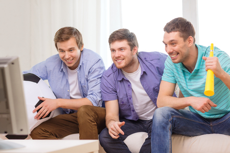 friendship, sports and entertainment concept - happy male friends with football and vuvuzela supporting football team at home photo