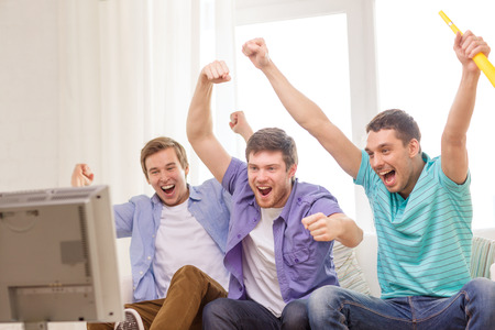 cheering fans: friendship, sports and entertainment concept - happy male friends with vuvuzela watching sports on tv