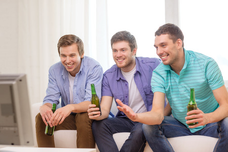 friendship, sports and entertainment concept - happy male friends with beer watching tv at home photo