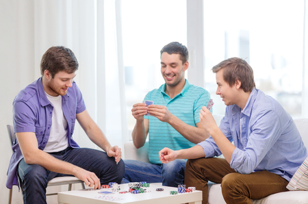 leisure, games and lifestyle concept - happy three male friends playing poker at home photo