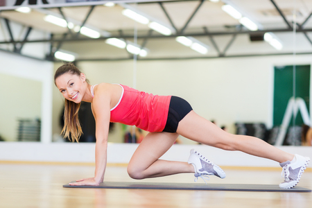 fitness, sport, training, gym and lifestyle concept - beautiful sporty woman doing exercise on the floor at gym photo