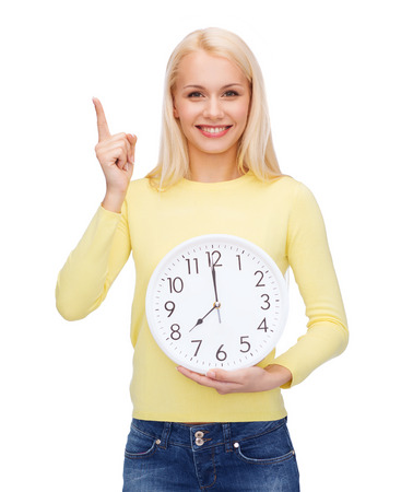 wall watch: time, education and people concept - smiling young woman with wall clock showing 8 and finger up