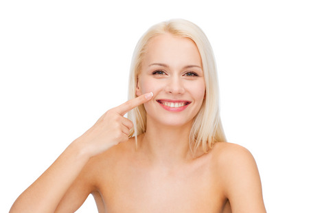 touching noses: health and beauty concept - smiling young woman pointing to her nose
