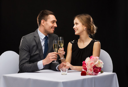 restaurant, couple and holiday concept - smiling couple with glass of champagne looking at each other at restaurant photo
