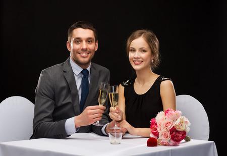 Glasses of champagne and candles: nhà hàng, cặp vợ chồng và nghỉ khái niệm - mỉm cười đôi với ly rượu sâm banh nhìn nhau tại nhà hàng