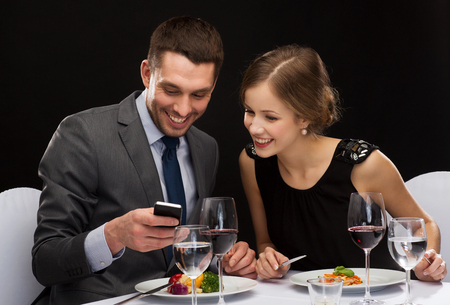 restaurant, technology, couple and holiday concept - smiling couple taking picture of main course with smartphone camera at restaurant photo