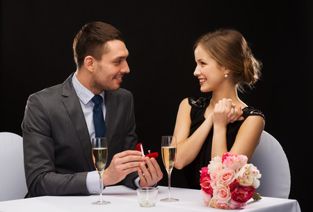 diamond jewellery: restaurant, couple and holiday concept - smiling man proposing to his girlfriend at restaurant Stock Photo