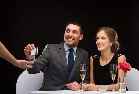 paying: restaurant, couple and holiday concept - smiling couple paying for dinner with credit card at restaurant