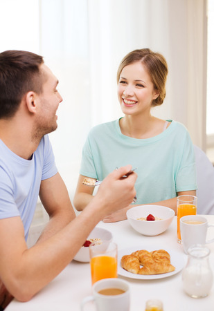 bowl of cereal: food, home, couple and happiness concept - smiling couple having breakfast at home Stock Photo