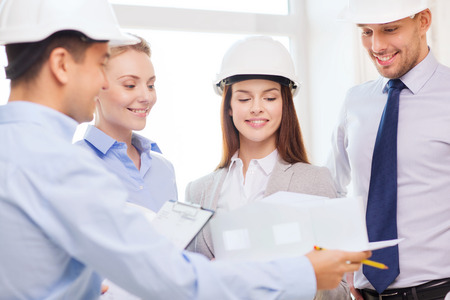 corporate meeting: business, architecture and office concept - happy team of architects in office Stock Photo