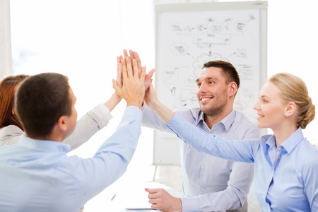 young entrepreneurs: success, business, office and winning concept - happy business team giving high five in office Stock Photo
