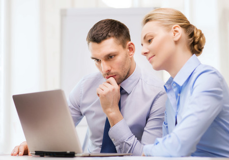 conference call: business, technology and office concept - serious businessman and businesswoman with laptop computer at office Stock Photo