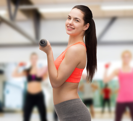 sport, exercising and healthcare concept - young sporty woman with light dumbbells photo