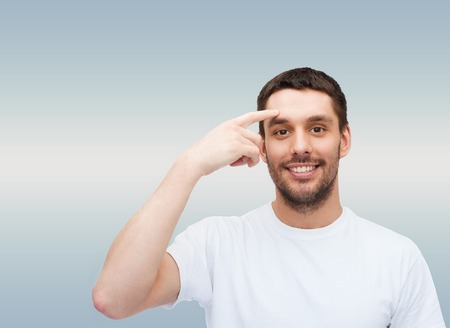 forehead: health and beauty concept - smiling young handsome man pointing to forehead Stock Photo