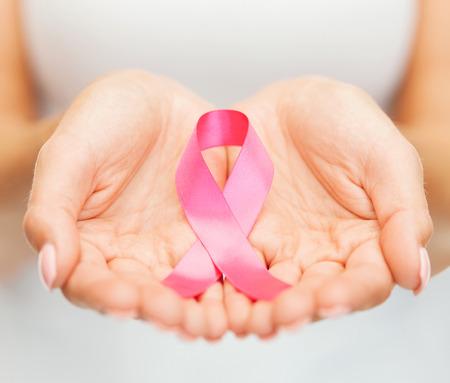 gezondheid en geneeskunde concept - vrouw handen die roze borstkanker bewustzijn lint